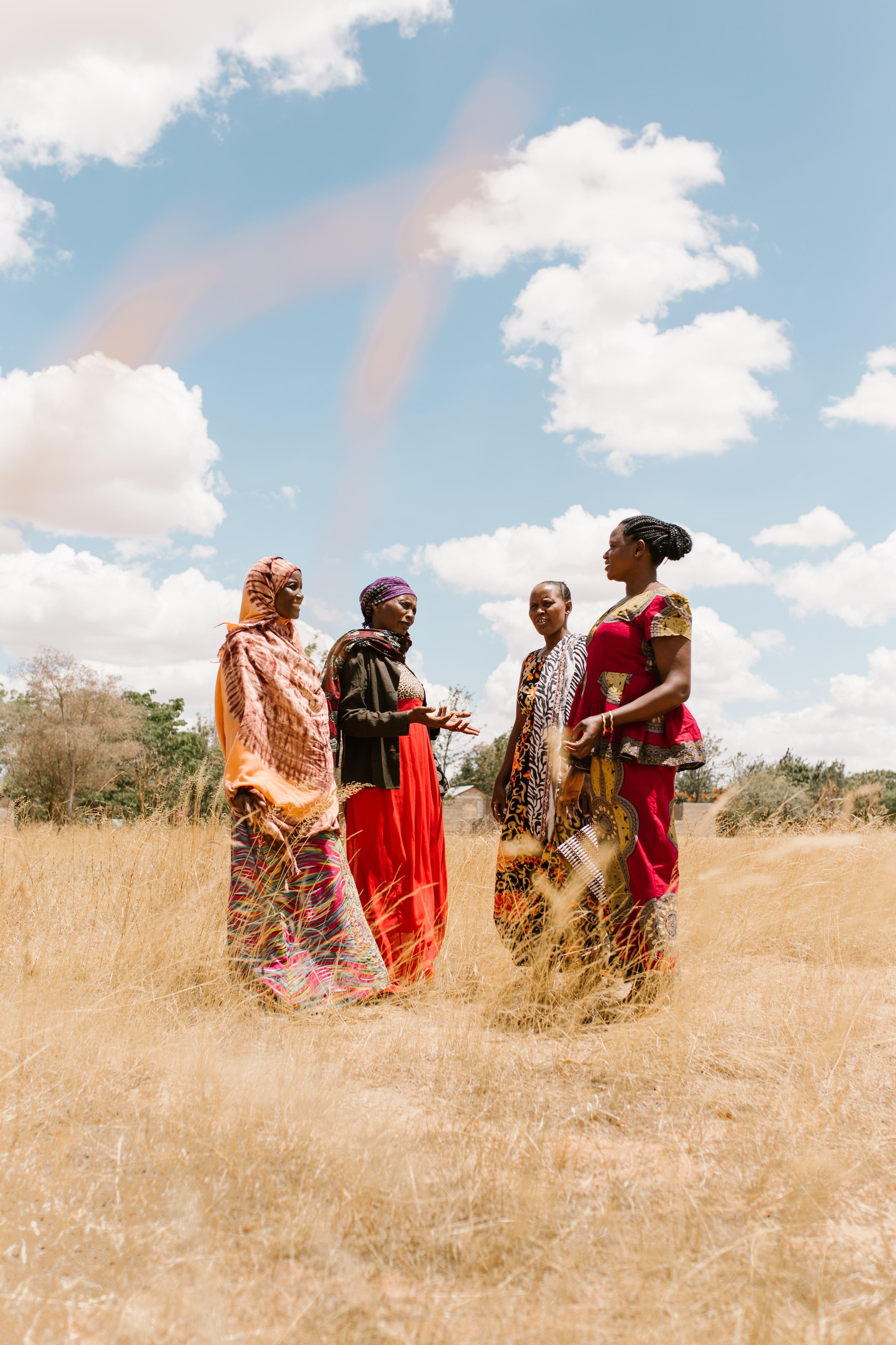 Fridian fra Tanzania står i en åker sammen med tre andre kvinner og snakker med dem om skadene kjønnslemlestelse av jenter. Foto av Sam Vox.