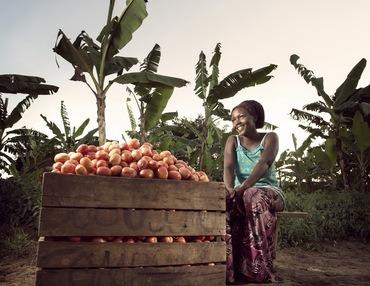 Ung kvinne sitter på en kasse på bakken foran et berg av tomater som hun skal selge. Hun smiler.