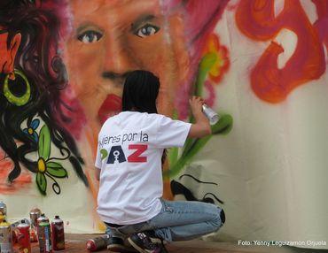 Bildet viser en colombiansk kvinne som tagger et kvinneansikt på en hvit vegg. På ryggen på t-skjorta hennes står det Mujeres por la paz, som betyr Kvinner for fred.