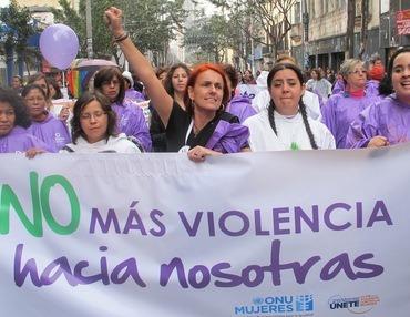 Kvinner fra Latin Amerika marsjerer i gatene i Bogota med et banner med påskrift som krever slutt på vold mot kvinner.